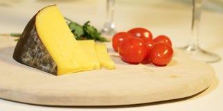 Gesneden gele kaas en kleine rode tomaten Stock Foto