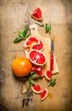 Gesneden grapefruit op een houten Raad met bladeren royalty-vrije stock foto
