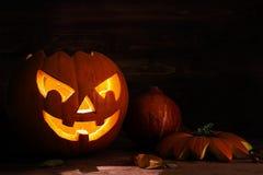 Gesneden Halloween-pompoen met een eng gloeiend gezicht op donkere rusti royalty-vrije stock afbeeldingen