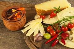 Gesneden harde kaas op de keukenraad Productie van kazen op het landbouwbedrijf Kruidige kaas, tomaten, knoflook, Spaanse pepers, Stock Afbeeldingen