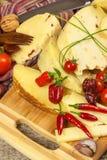 Gesneden harde kaas op de keukenraad Productie van kazen op het landbouwbedrijf Kruidige kaas, tomaten, knoflook, Spaanse pepers, Royalty-vrije Stock Foto's