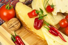 Gesneden harde kaas op de keukenraad Productie van kazen op het landbouwbedrijf Kruidige kaas, tomaten, knoflook, Spaanse pepers, Royalty-vrije Stock Afbeelding