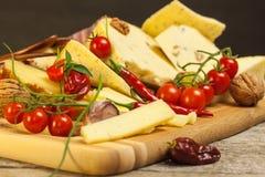 Gesneden harde kaas op de keukenraad Productie van kazen op het landbouwbedrijf Kruidige kaas, tomaten, knoflook, Spaanse pepers, stock fotografie