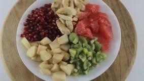 Gesneden kiwi, banaan, grapefruit, peer en granaatappel die op een witte plaat roteren Ingrediënten voor fruitsalade stock videobeelden