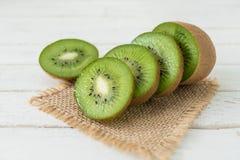 Gesneden kiwifruit op witte houten achtergrond met jute Royalty-vrije Stock Fotografie