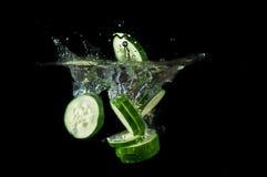 Gesneden komkommer bespattend water Stock Foto