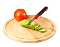 Gesneden komkommer en tomaat op een scherpe raad Stock Afbeeldingen