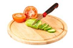 Gesneden komkommer en tomaat op een scherpe raad Royalty-vrije Stock Foto's