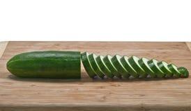 Gesneden komkommer horizontaal op scherpe raad Stock Afbeelding