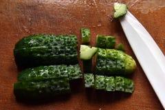 Gesneden komkommerplakken en een ceramisch mes stock foto