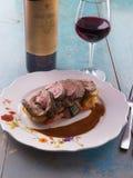 Gesneden middelgroot zeldzaam die lapje vlees met geroosterde groenten en rode wijn wordt gediend Stock Afbeelding