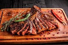 Gesneden middelgroot zeldzaam geroosterd lapje vlees op rustieke scherpe raad met rozemarijn en kruiden, donkere rustieke houten  Stock Afbeelding