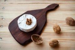 Gesneden om camembertkaas op een houten raad met noten Stock Foto's