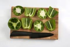 Gesneden paprika's met een ceramisch mes op een houten raad Royalty-vrije Stock Afbeeldingen