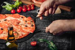Gesneden plak van pizza ter beschikking met kaas, forel, tomaten, olijven en garnalen op schoolbord royalty-vrije stock foto's