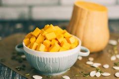 Gesneden pompoenen in plaat met zaden op keukenlijst Stock Afbeelding