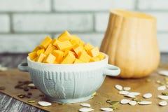 Gesneden pompoenen in plaat met zaden op keukenlijst Royalty-vrije Stock Foto