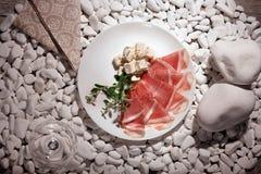 Gesneden prosciutto, de kaasroquefort en de kruiden op een wit schommelen achtergrond Hoogste mening van een plaat met luxueuze s Stock Foto's