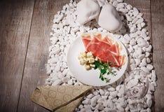 Gesneden prosciutto, kaasroquefort en groene kruiden op een houten achtergrond Hoogste mening van een plaat met luxueuze snacks Royalty-vrije Stock Afbeeldingen