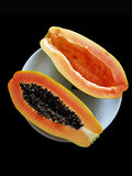 Gesneden rijpe papaja op zwarte achtergrond Stock Afbeeldingen