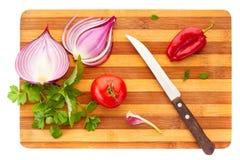 Gesneden rode ui, tomatoe, peper, knoflook, basilicum en peterselie met mes op houten raad over witte achtergrond Royalty-vrije Stock Afbeeldingen