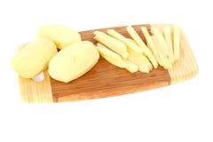 Gesneden ruwe aardappels op een hakbord Stock Foto's