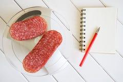 Gesneden ruwe worst op een keukenschaal, naast een notitieboekje en een vulpen De hoeveelheid calorieën, proteïne en vet in voeds stock foto