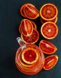 Gesneden Siciliaans rood sinaasappelen en jus d'orange in glaskruik op zwarte steenachtergrond Hoogste mening Royalty-vrije Stock Foto