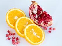 Gesneden sinaasappel en granaatappel op een lichtblauwe achtergrond Stock Afbeeldingen
