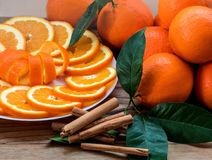 Gesneden sinaasappel met spiraalvormige schil op de plaat en groupe van sinaasappelen op de houten lijst stock foto