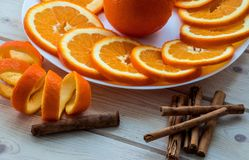 Gesneden sinaasappel met spiraalvormige schil op de plaat en de pijpjes kaneel op de houten lijst stock foto's