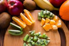 Gesneden sinaasappelen en kiwien op een scherpe raad Stock Foto's