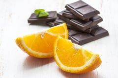 Gesneden sinaasappelen met donkere chocolade op een witte houten achtergrond Stock Foto's