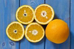 Gesneden sinaasappelen op een blauwe houten achtergrond royalty-vrije stock afbeeldingen