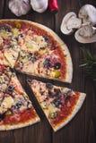 Gesneden smakelijke verse pizza met paddestoelen en worst op een houten achtergrond Stock Foto's