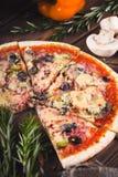 Gesneden smakelijke verse pizza met paddestoelen en worst op een houten achtergrond Stock Afbeeldingen