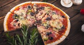 Gesneden smakelijke verse pizza met paddestoelen en worst op een houten achtergrond Stock Afbeelding
