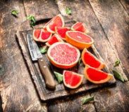 Gesneden stukken van grapefruit met een mes stock foto's