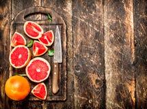 Gesneden stukken van grapefruit met een mes royalty-vrije stock afbeeldingen