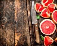 Gesneden stukken van grapefruit met een mes royalty-vrije stock fotografie