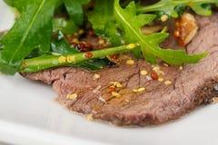 Gesneden stukken van voorbereide vlees en arugula, kruiden royalty-vrije stock afbeelding