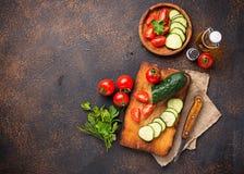 Gesneden tomaat en komkommer op scherpe raad Stock Afbeelding