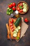 Gesneden tomaat en komkommer op scherpe raad Stock Afbeeldingen