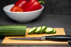 Gesneden verse komkommer op een knipselraad met een mes en een ceramische plaat van groenten stock foto's