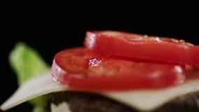 Gesneden verse tomaten en ingelegde komkommersdaling op kaas in een hamburger stock video