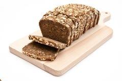 Gesneden volkorenbrood op keukenraad stock foto