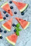 Gesneden watermeloen en bosbessen op de achtergrond van de ijsbuis stock afbeeldingen