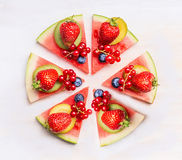 Gesneden watermeloenpizza met vruchten en bessen op witte houten achtergrond, hoogste mening Gezond voedsel stock afbeelding