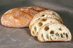 Gesneden wit brood die in stro op grijs linnentafelkleed liggen Stock Fotografie