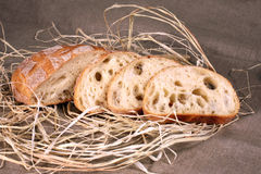 Gesneden wit brood die in stro op grijs linnentafelkleed liggen Royalty-vrije Stock Afbeelding